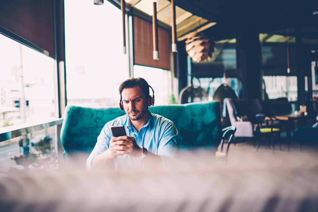 Man listening to music on phone in coffee shop